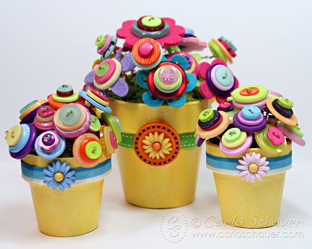 Colorful flowers made of buttons in yellow flowerpots.