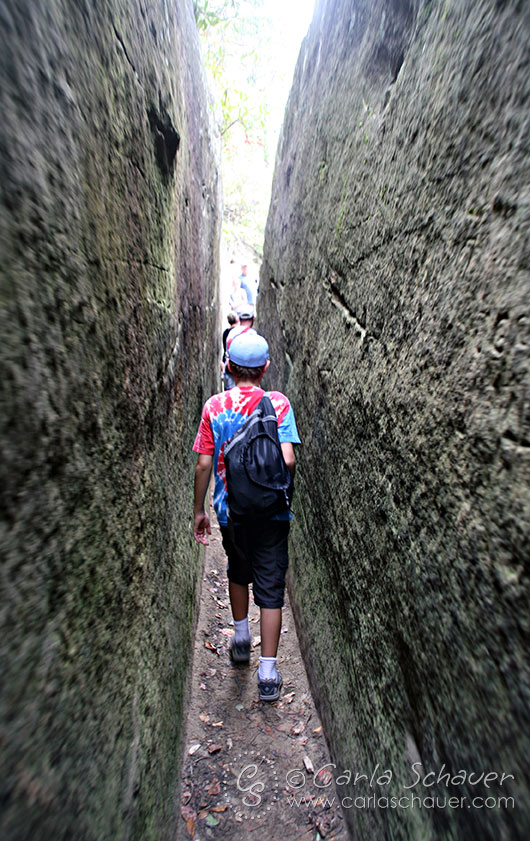 Teenager walking through rock tunnel