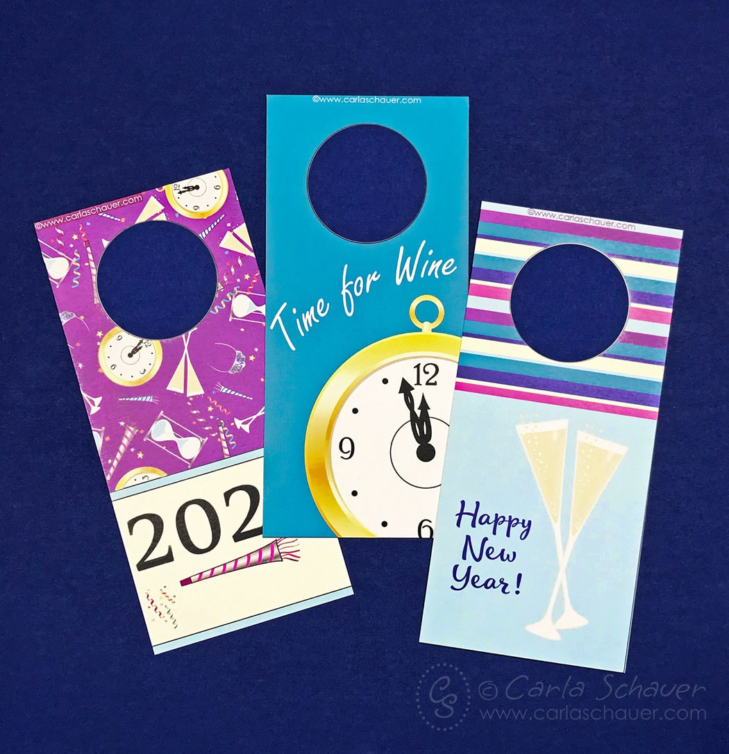 3 New Year's Eve wine bottle tags laying on blue backgroune