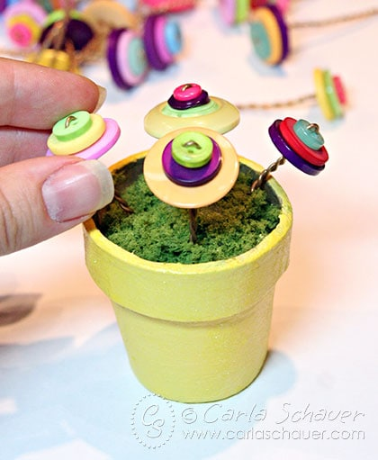 Add button flowers to topiary flowerpots, tutorial from Carla Schauer Designs