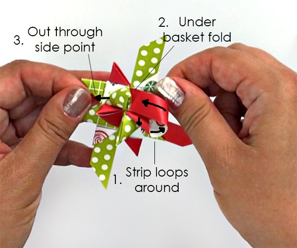 Hands folding paper strips to make German star ornaments.