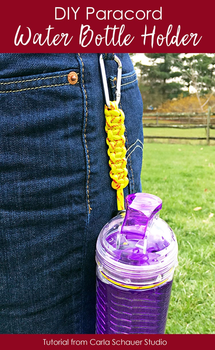 Yellow paracord bottle holder attached to belt loop and purple reusable bottle.