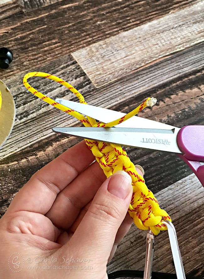 Trim ends of paracord when finished knotting. Tutorial for DIY water bottle holders on carlaschauer.com