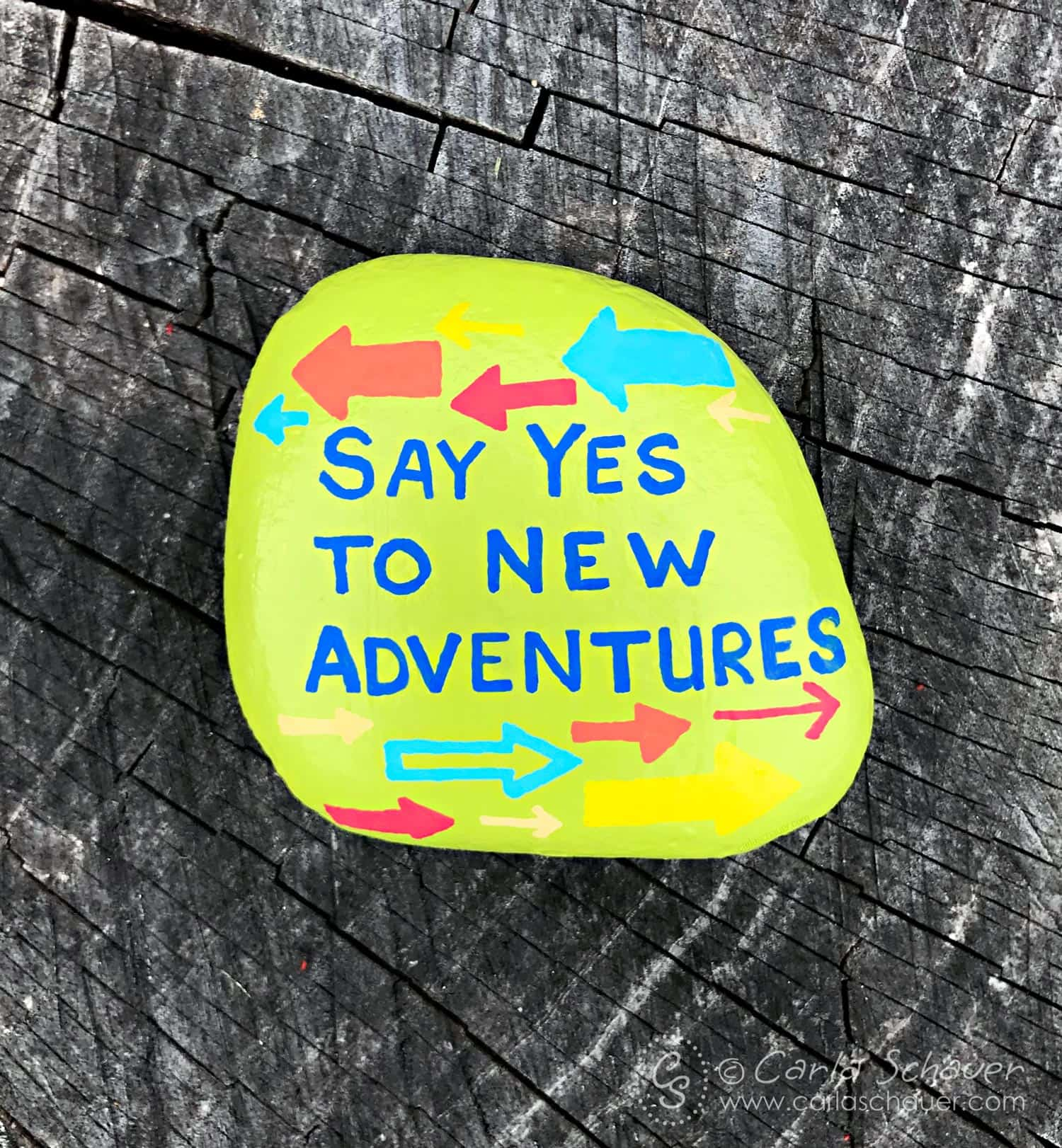 Adventure green painted rock with multicolored arrows on wood background