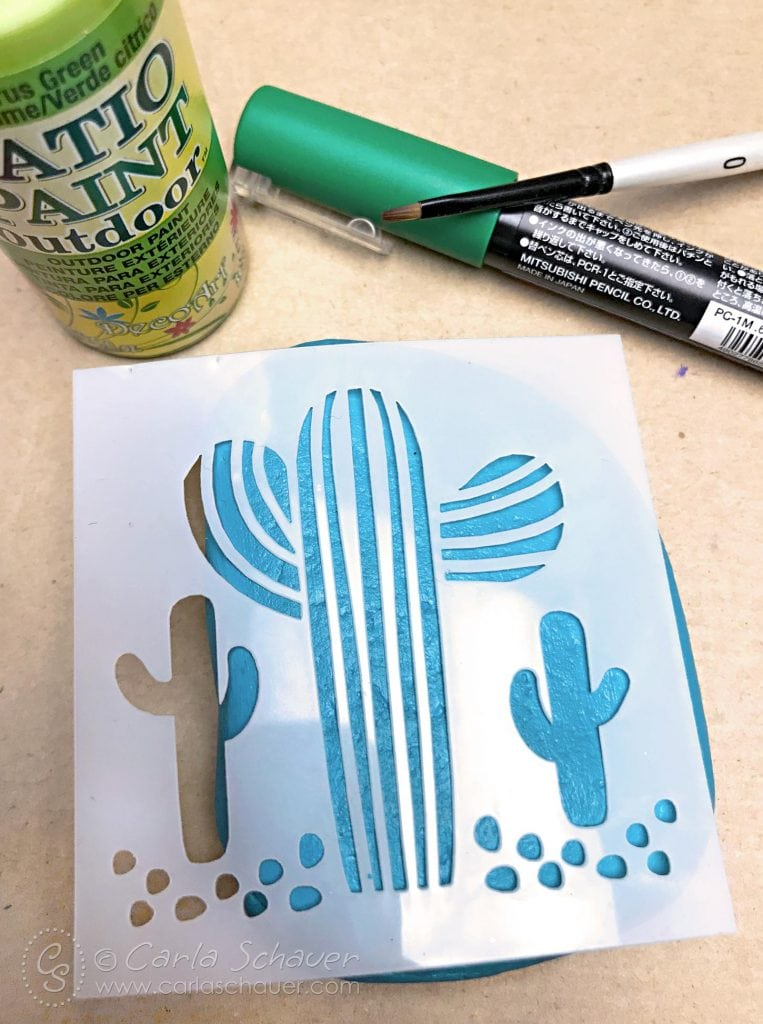 Cactus stencil on a blue painted rock, with green paint supplies.