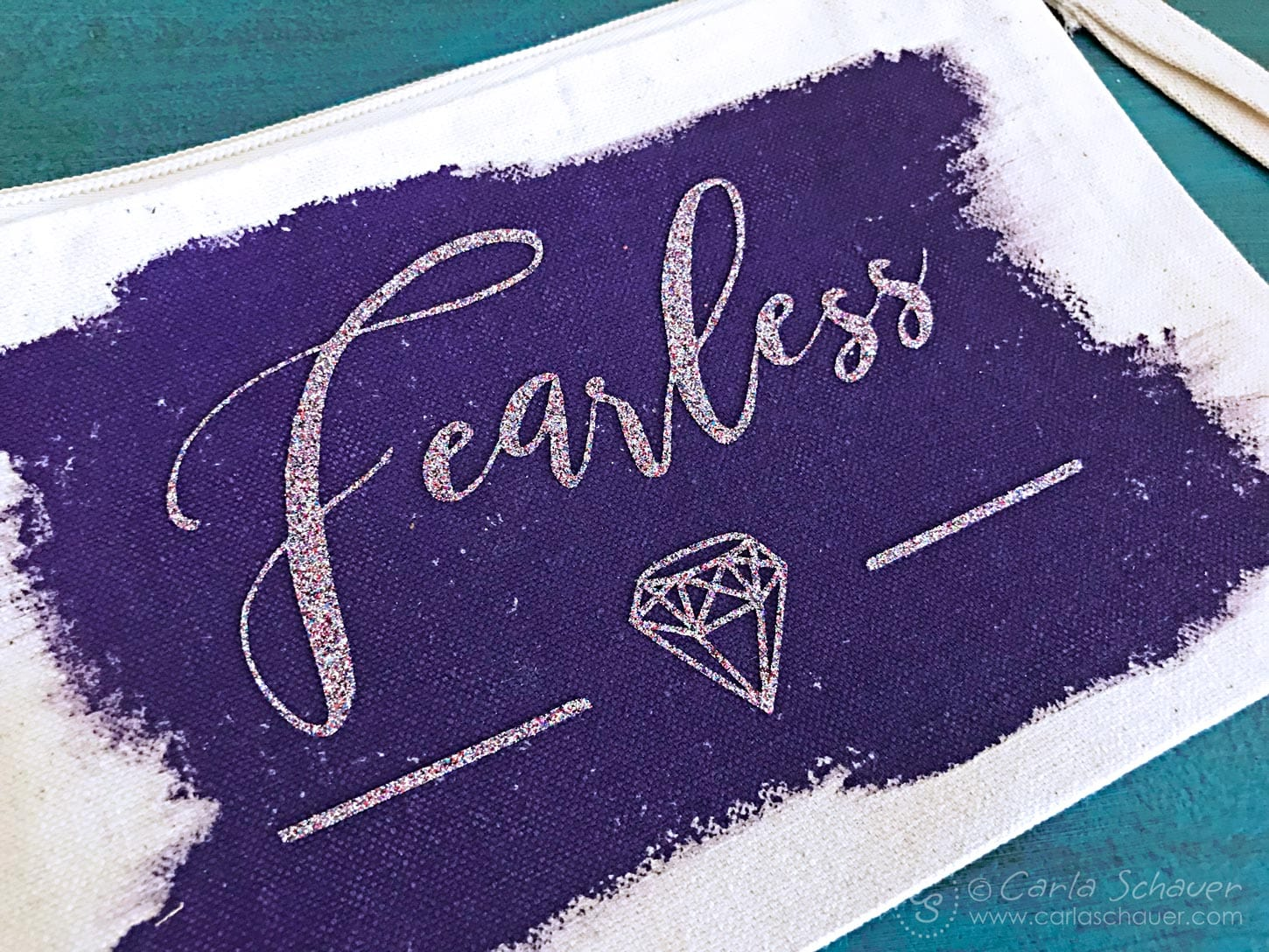 "Glitter gem and ""fearless"" text on purple painted canvas zipper pouch."