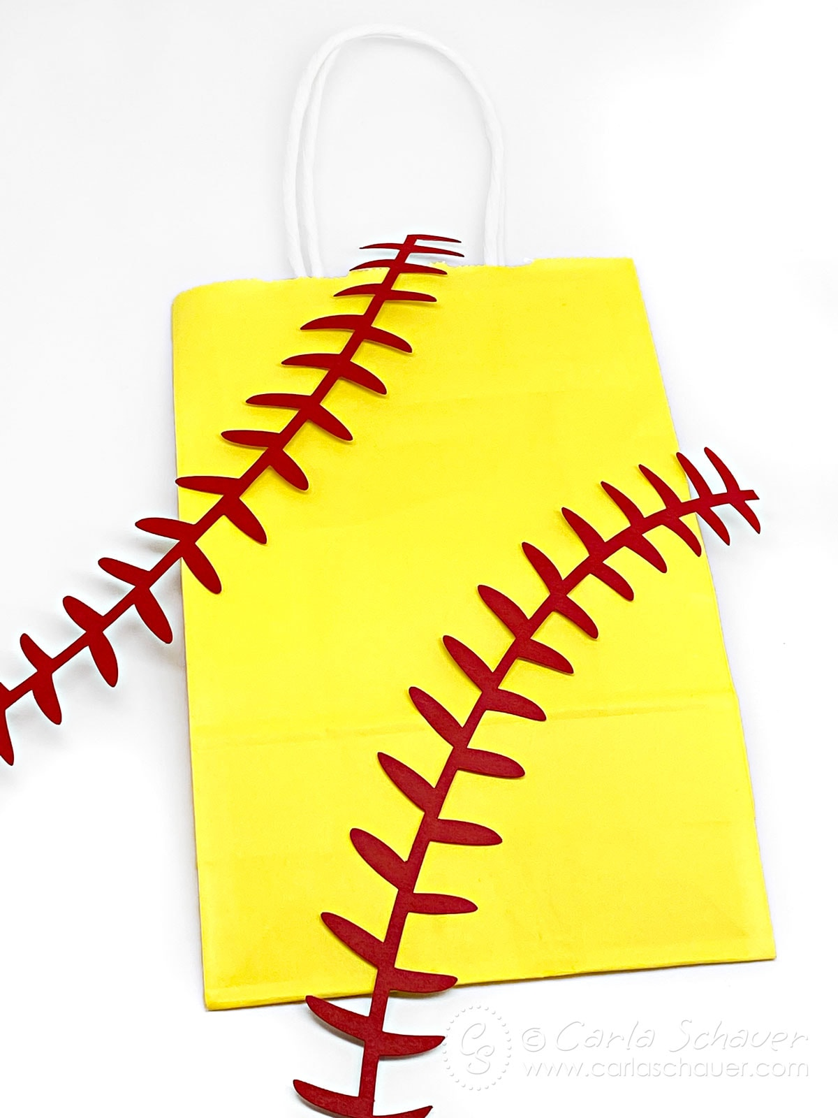 Yellow gift bag and paper softball laces on white background