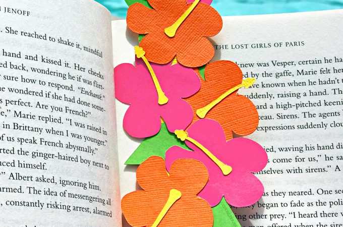 Hibiscus flower tropical bookmark in book next to pool.