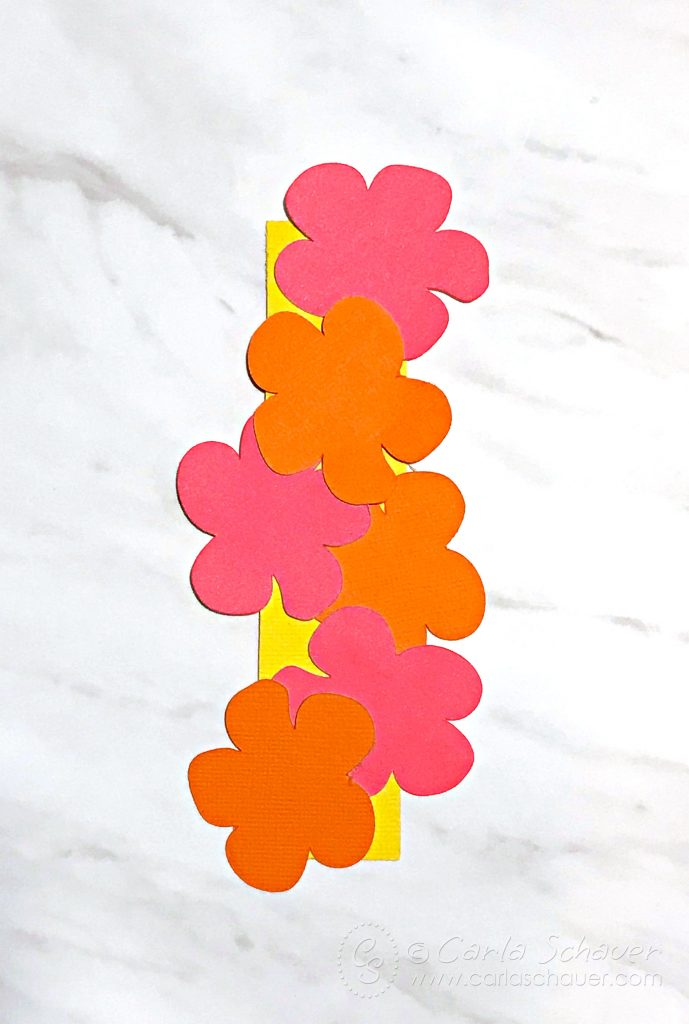 Pink and orange paper hibiscus flowers arranged on yellow rectangle.