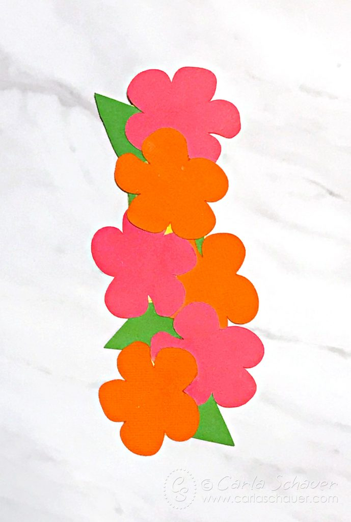 Pink and orange hibiscus flowers and green leaves arranged on marble background. Part of summer floral bookmark tutorial.
