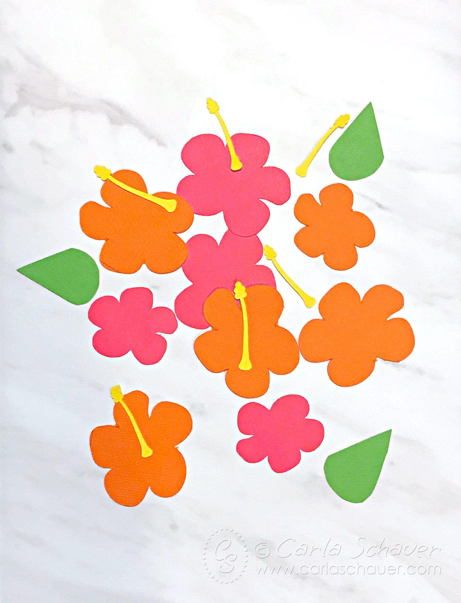 Orange and pink paper hibiscus flower cutouts on marble background. Part of summer floral bookmark tutorial.