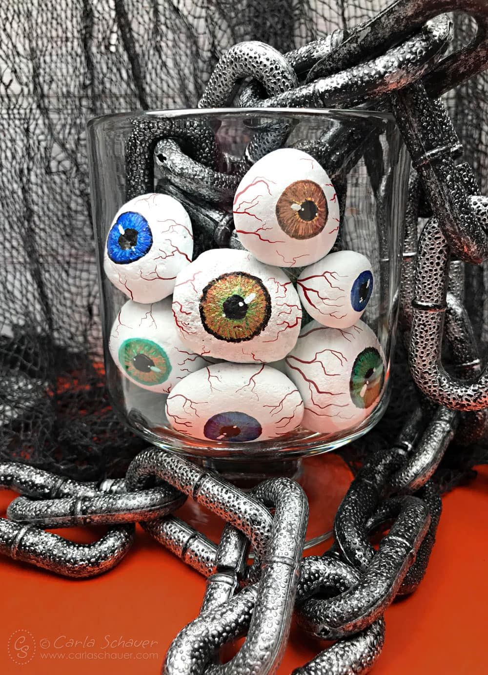 Painted rock eyeballs in jar with chain and black mesh background.