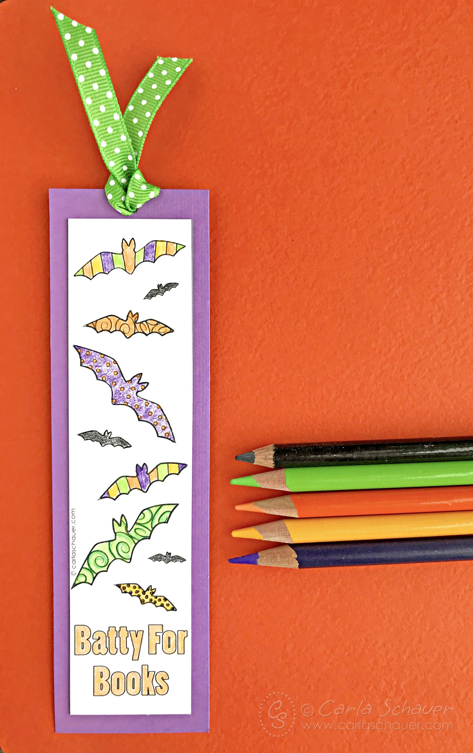Colored bat bookmark with green ribbon on orange background with colored pencils