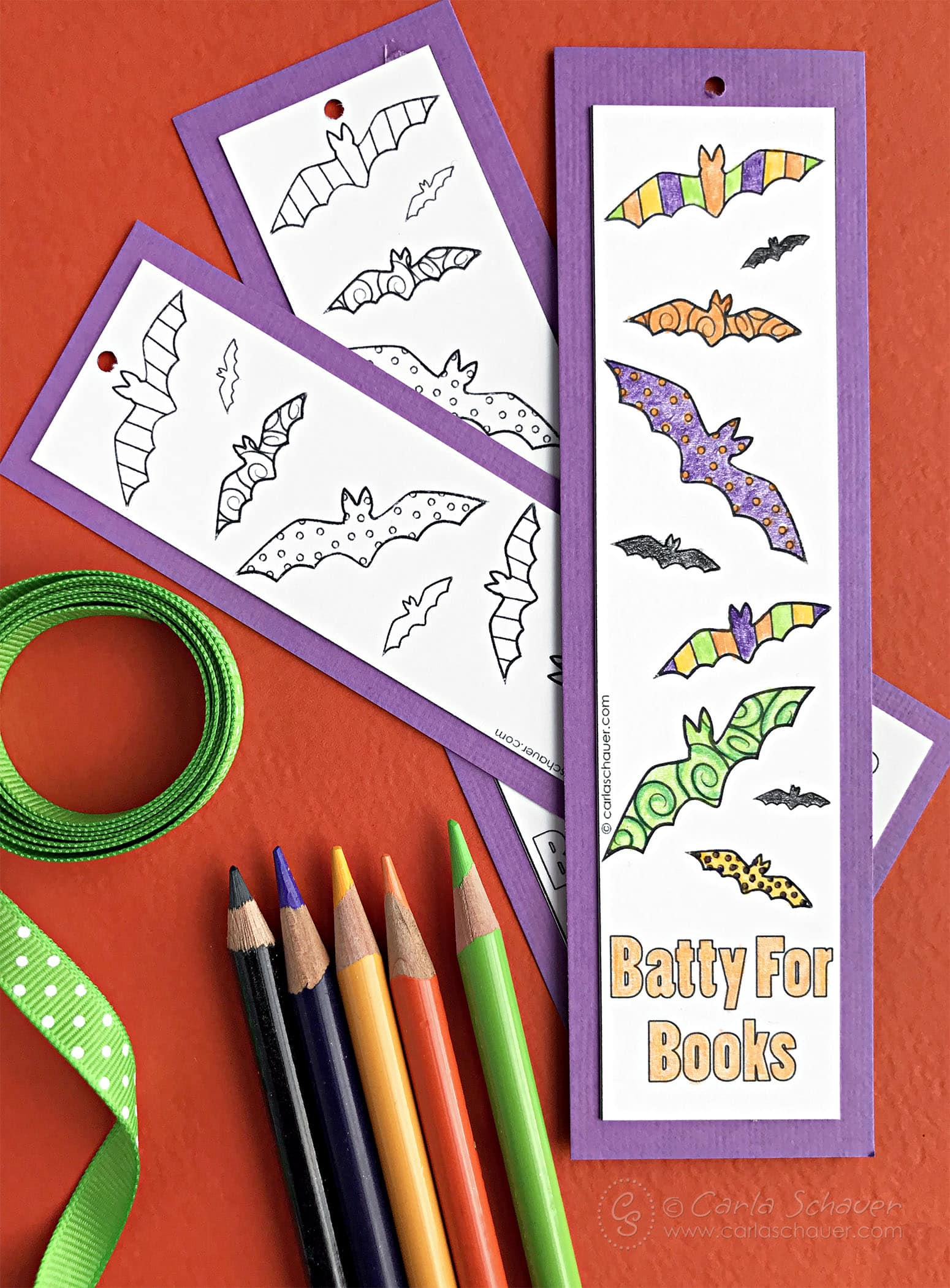 Halloween bat bookmarks with purple borders and colored pencils on orange background