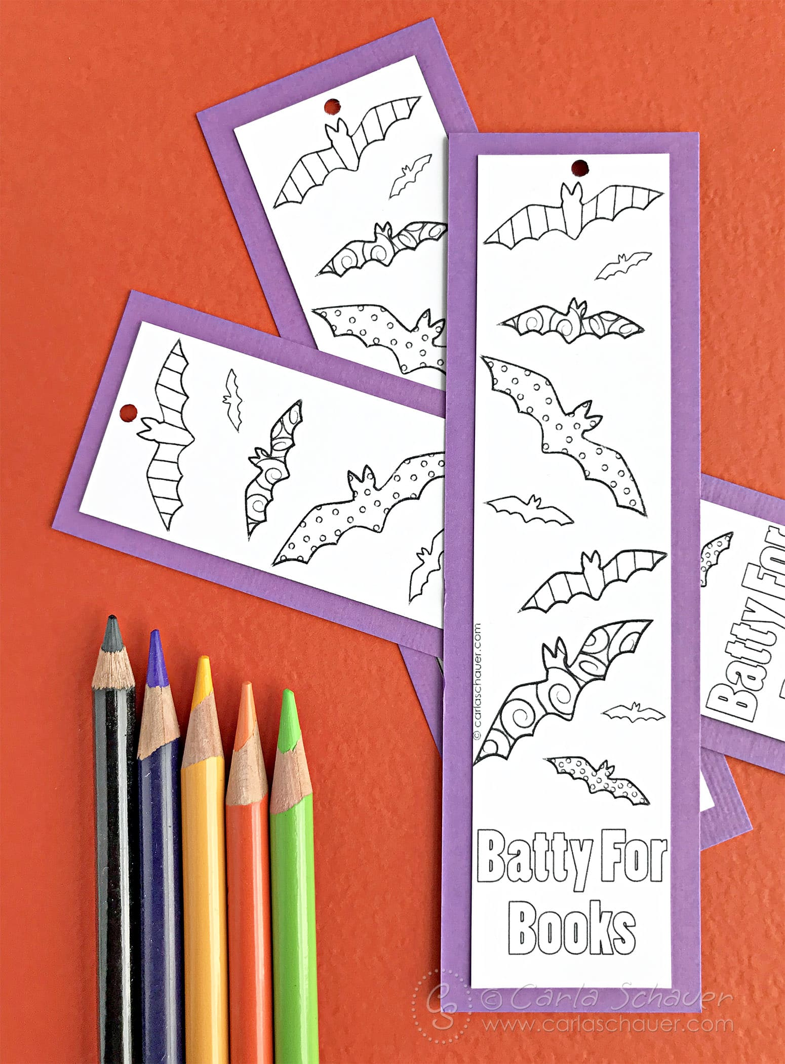 Black and white bat halloween bookmarks with purple borders on orange background with colored pencils.