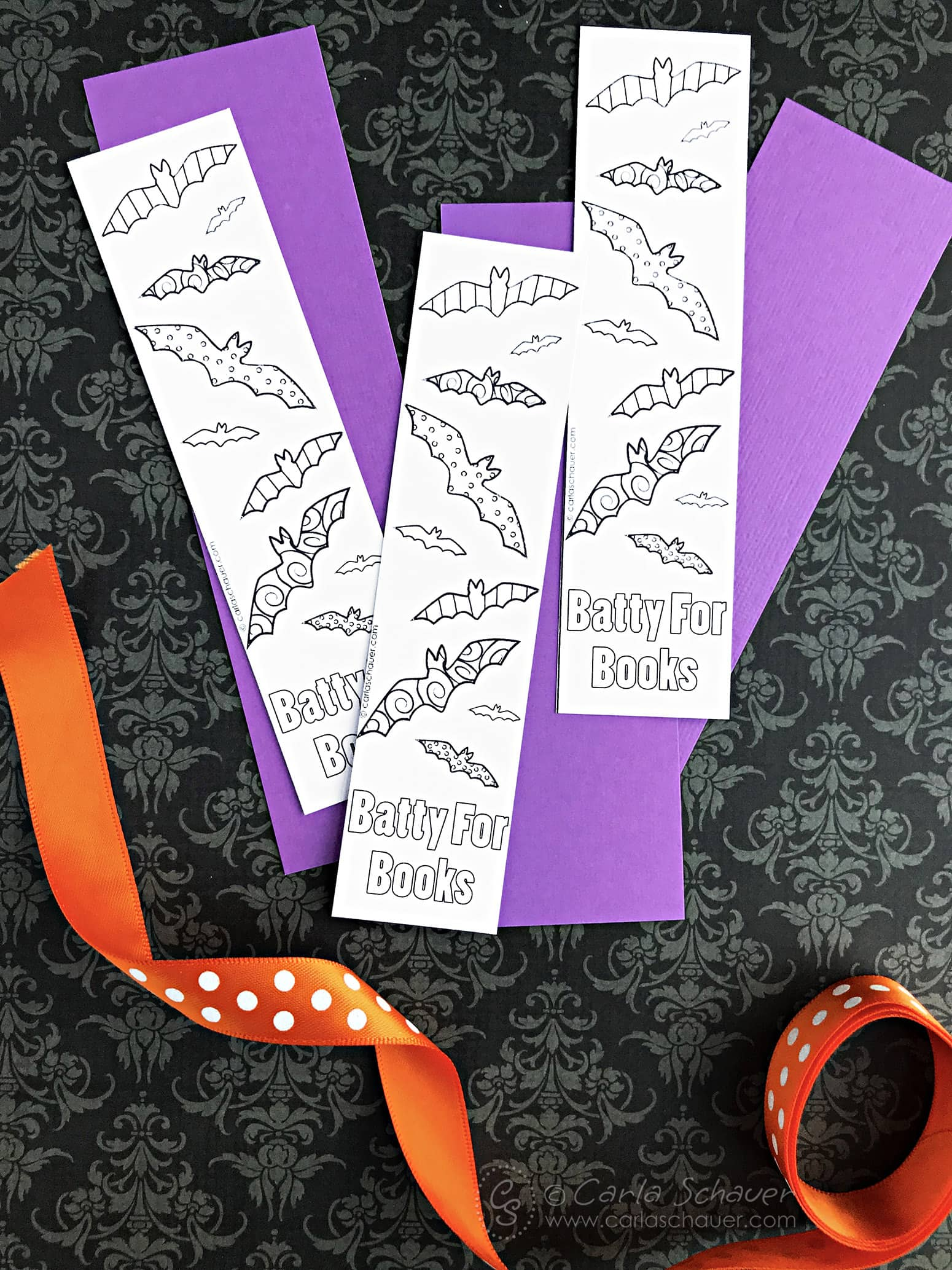 Cut out printed bat bookmarks, purple paper strips and orange ribbon on black background