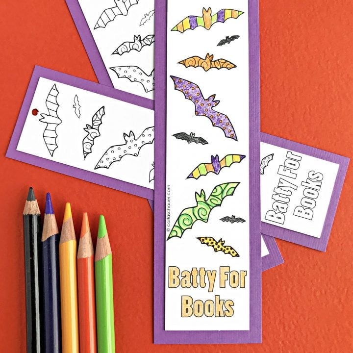 One colored, 2 uncolored DIY bat Halloween bookmarks with colored pencils on orange background.
