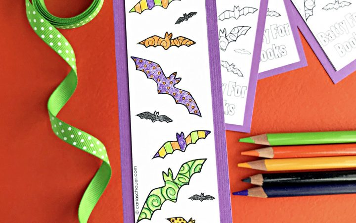 Colorful bat bookmark with colored pencils, ribbon, and uncolored bookmarks in background.