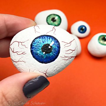 Halloween painted rock eyeball held in front of other painted eyeball rocks on orange background