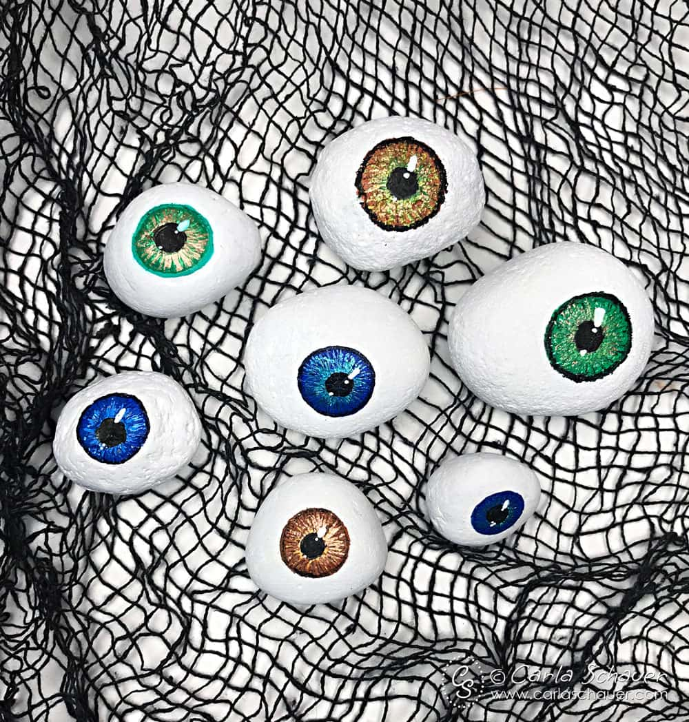 7 Painted rock eyeballs on black mesh background.
