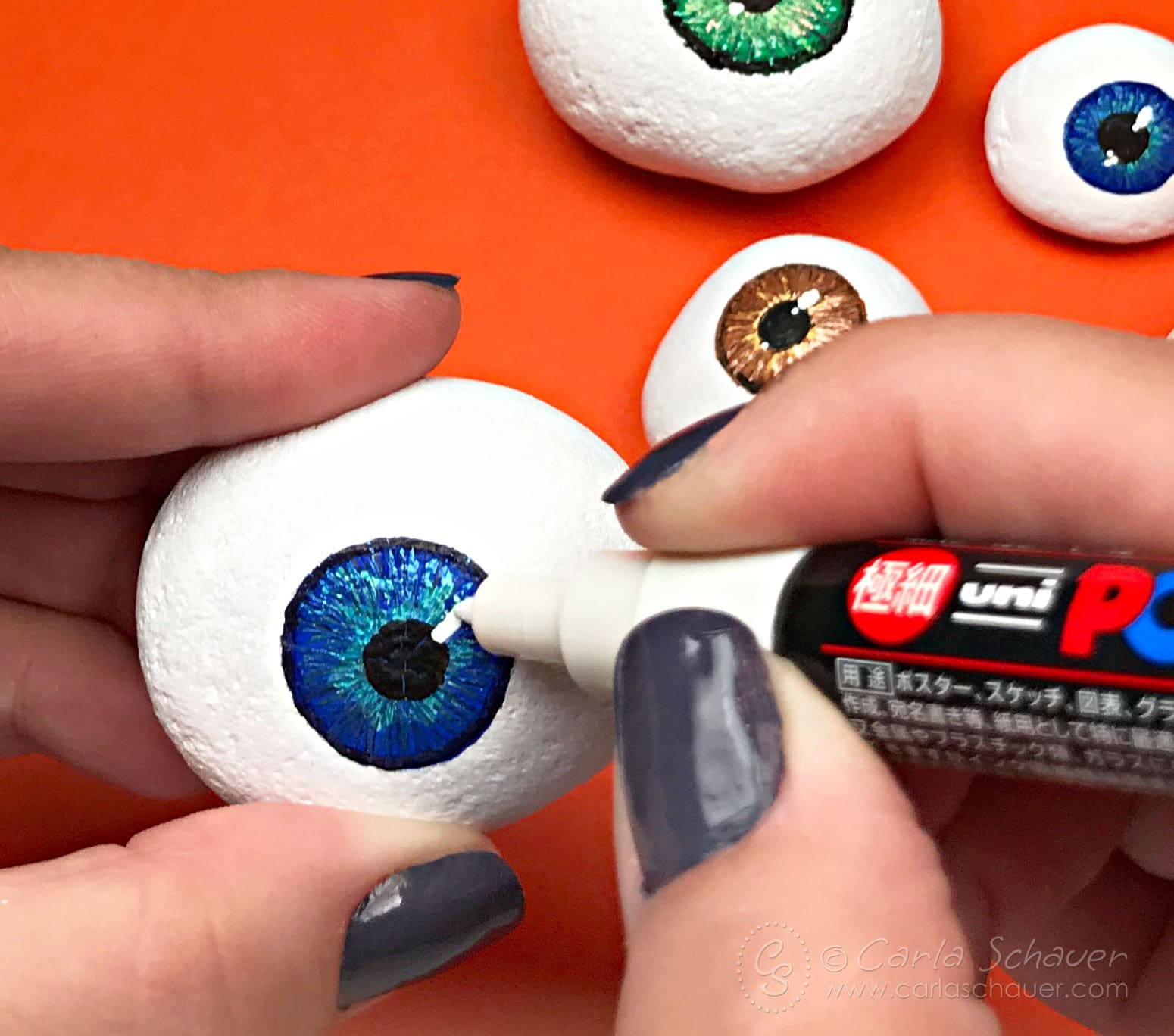 Hand drawing highlight on painted eyeball rock with white paint marker. Orange background