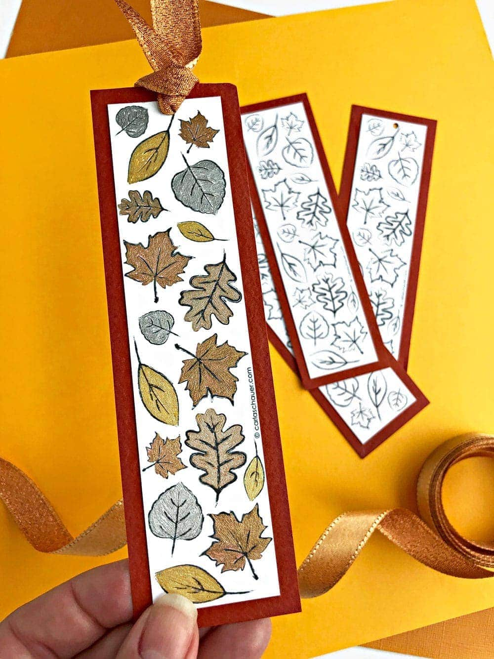 metallic colored leaf bookmark and uncolored leaf bookmarks on yellow background