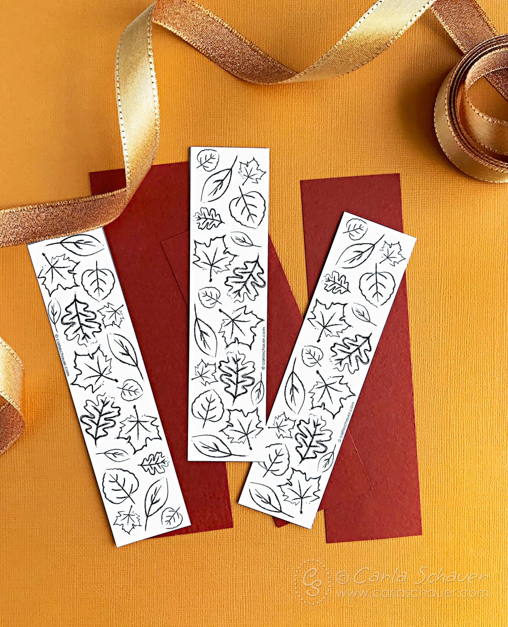 Cut out printable leaf bookmarks on rust colored paper strips.