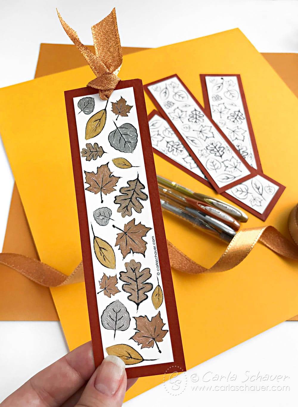 metallic colored leaf bookmark, gel pens, and uncolored leaf bookmarks on yellow background