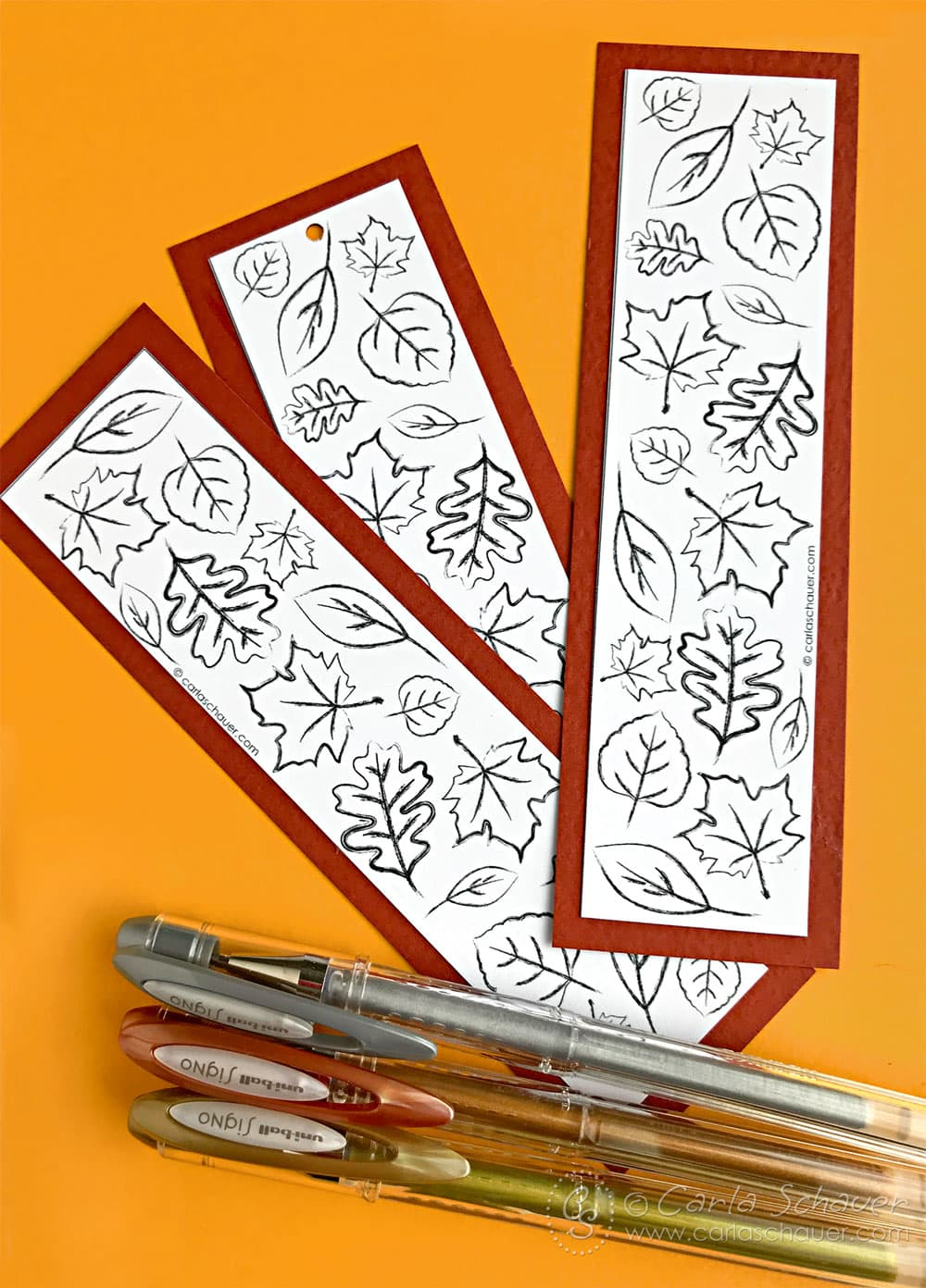 Rust colored matted DIY leaf bookmarks on gold background