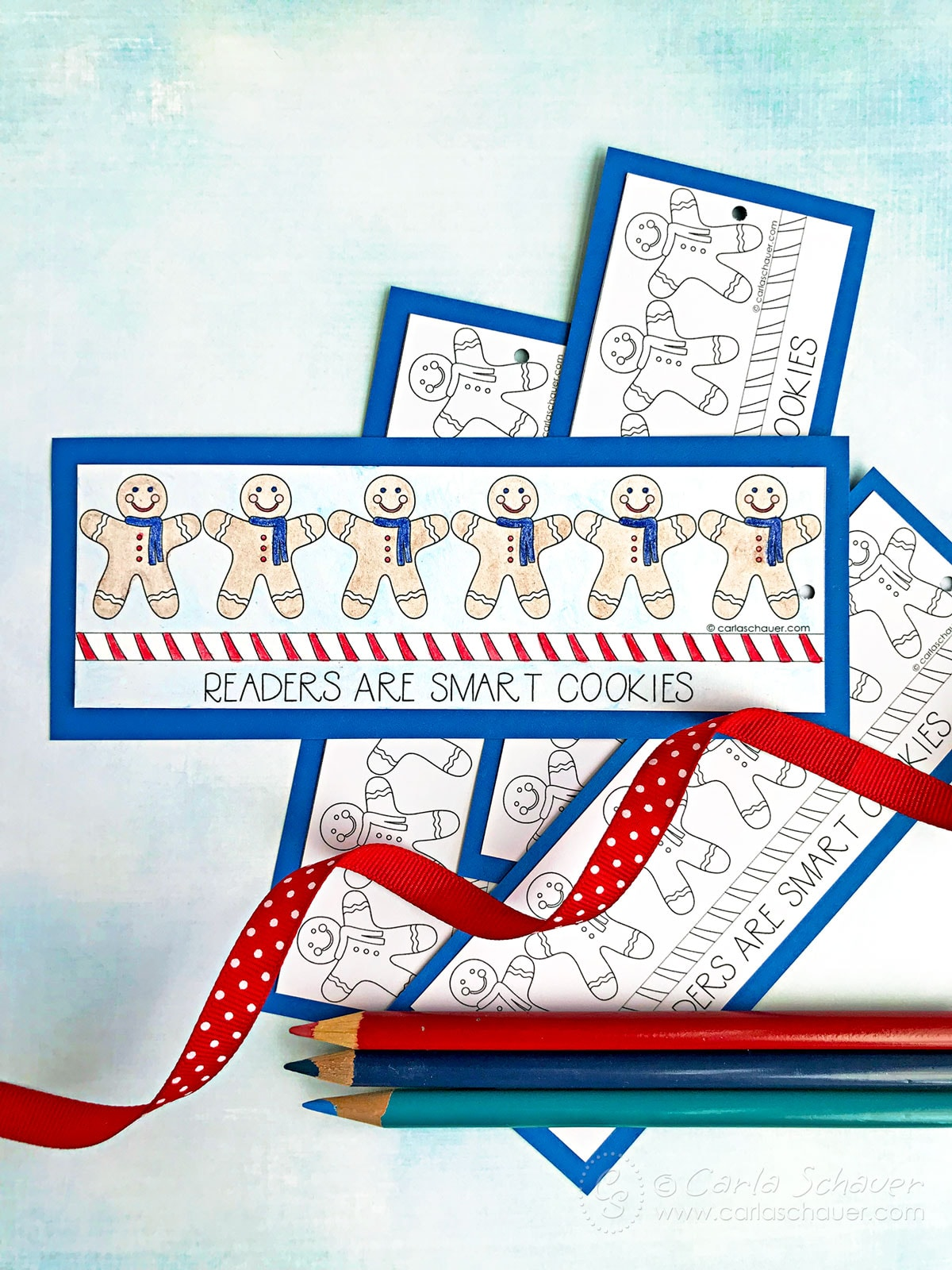 Gingerbread men colored bookmark in front of uncolored bookmarks and colored pencils.