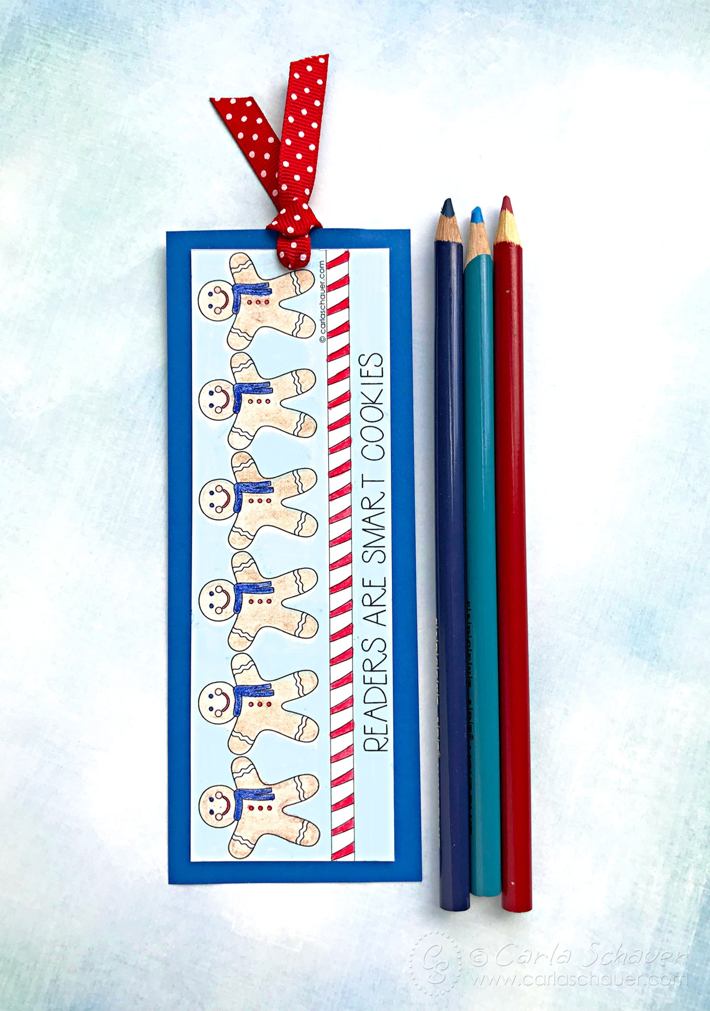 Printable winter bookmark after coloring, next to colored pencils on blue background.