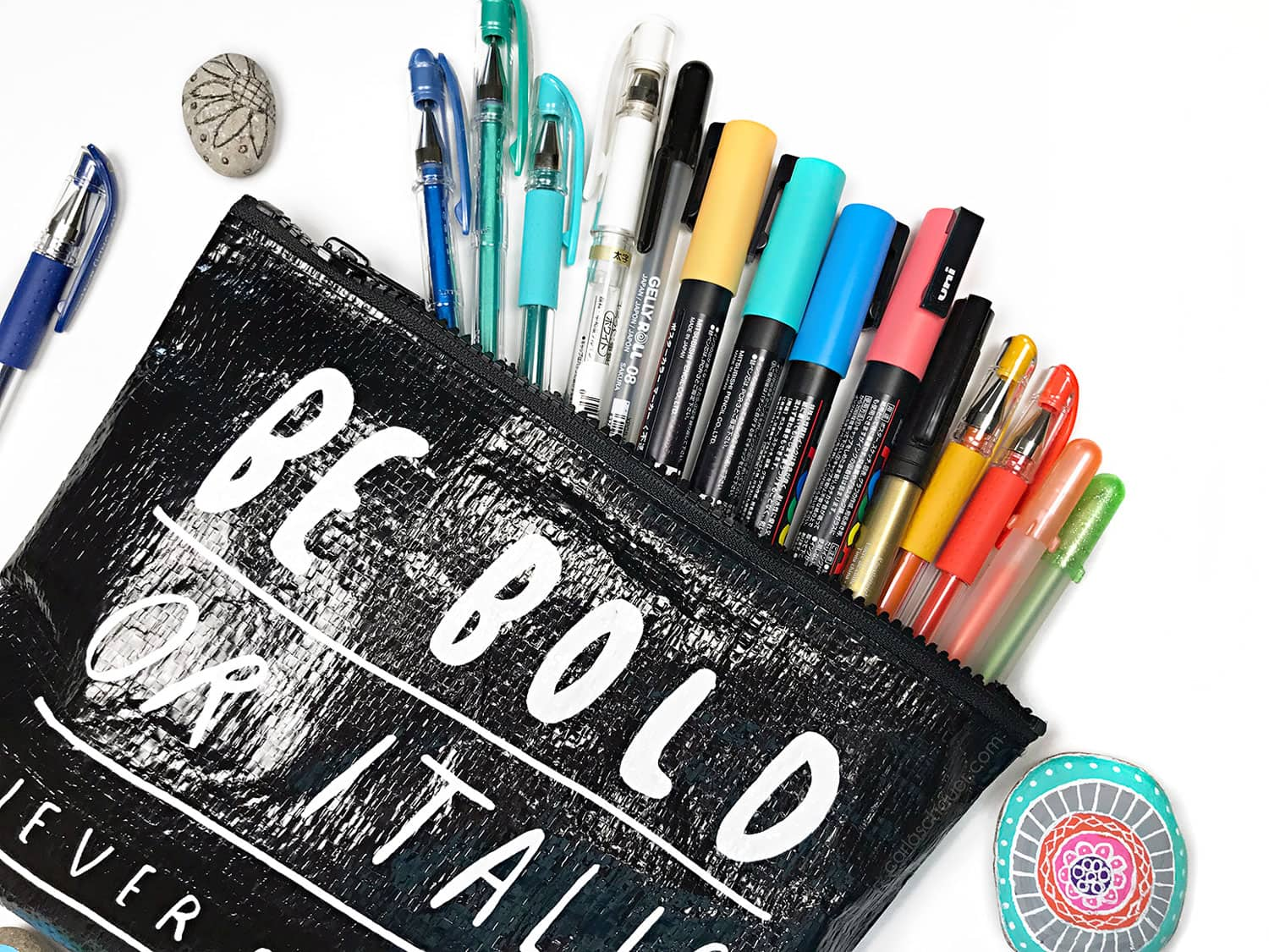 Black pouch of paint markers and gel pens, with painted rocks on white background.