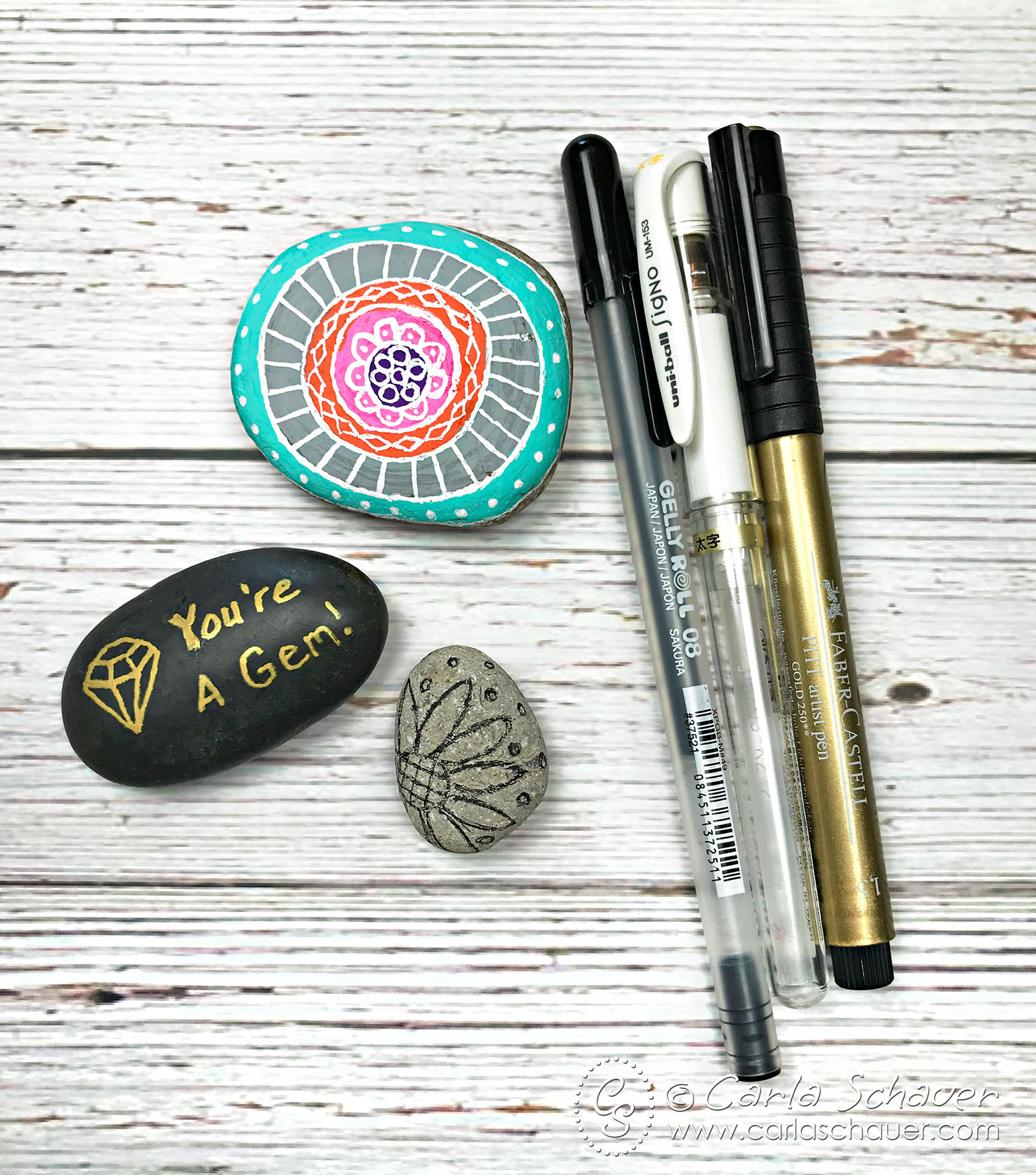3 pens and 3 decorated rocks on white wood background.