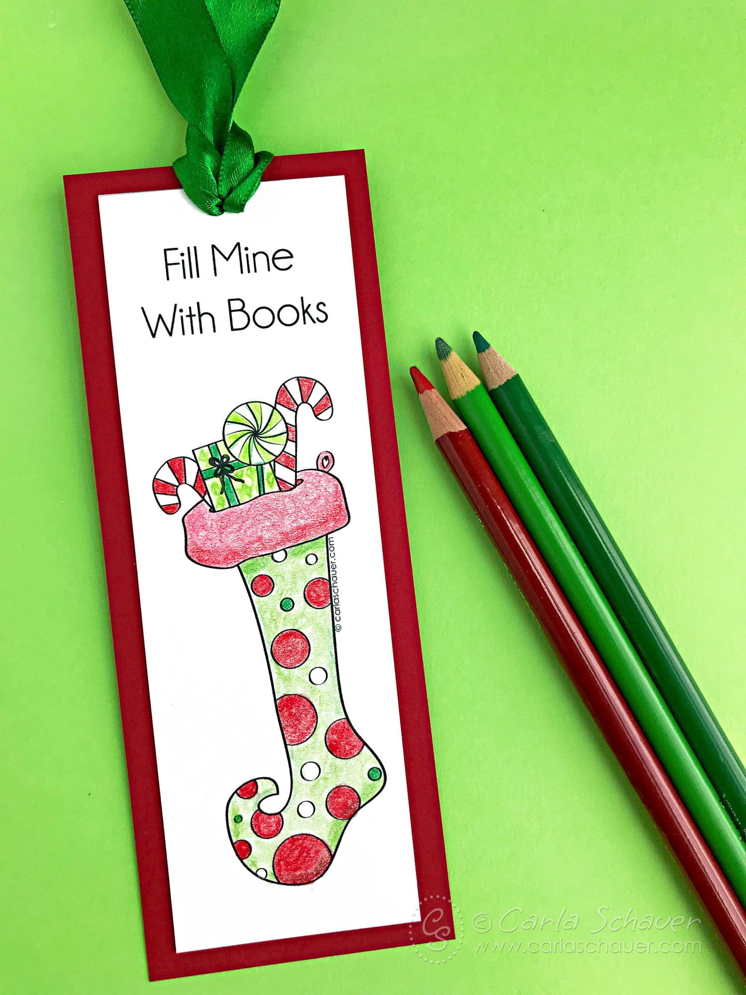 Colored stocking holiday printable bookmark with colored pencils on green background.