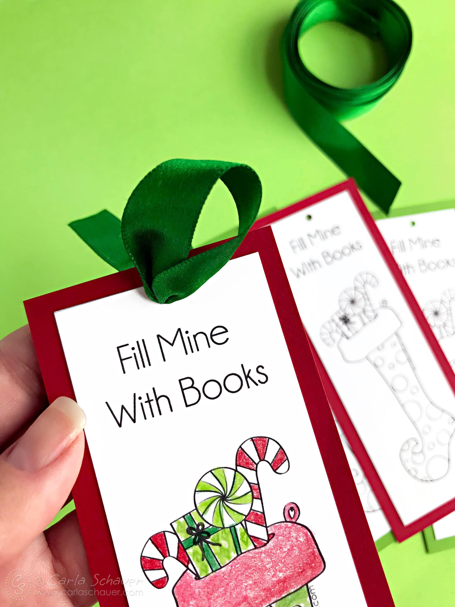 Green ribbon tied to printable Christmas bookmark craft.