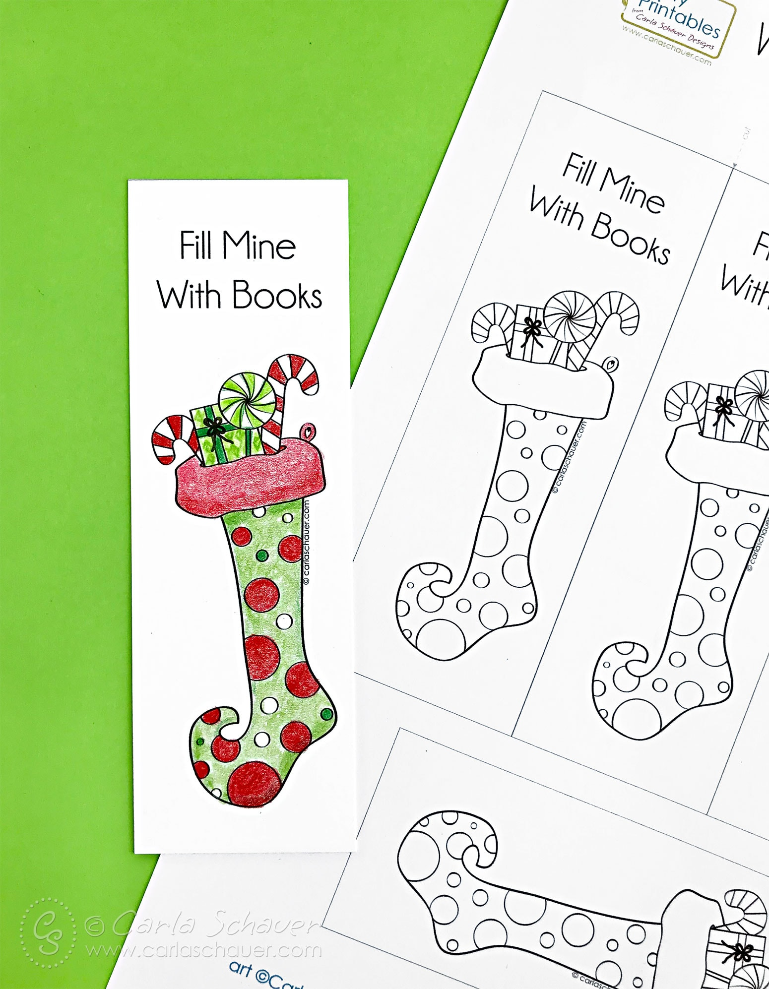 Red and green colored stocking bookmark and printable Christmas bookmark sheet on green background.