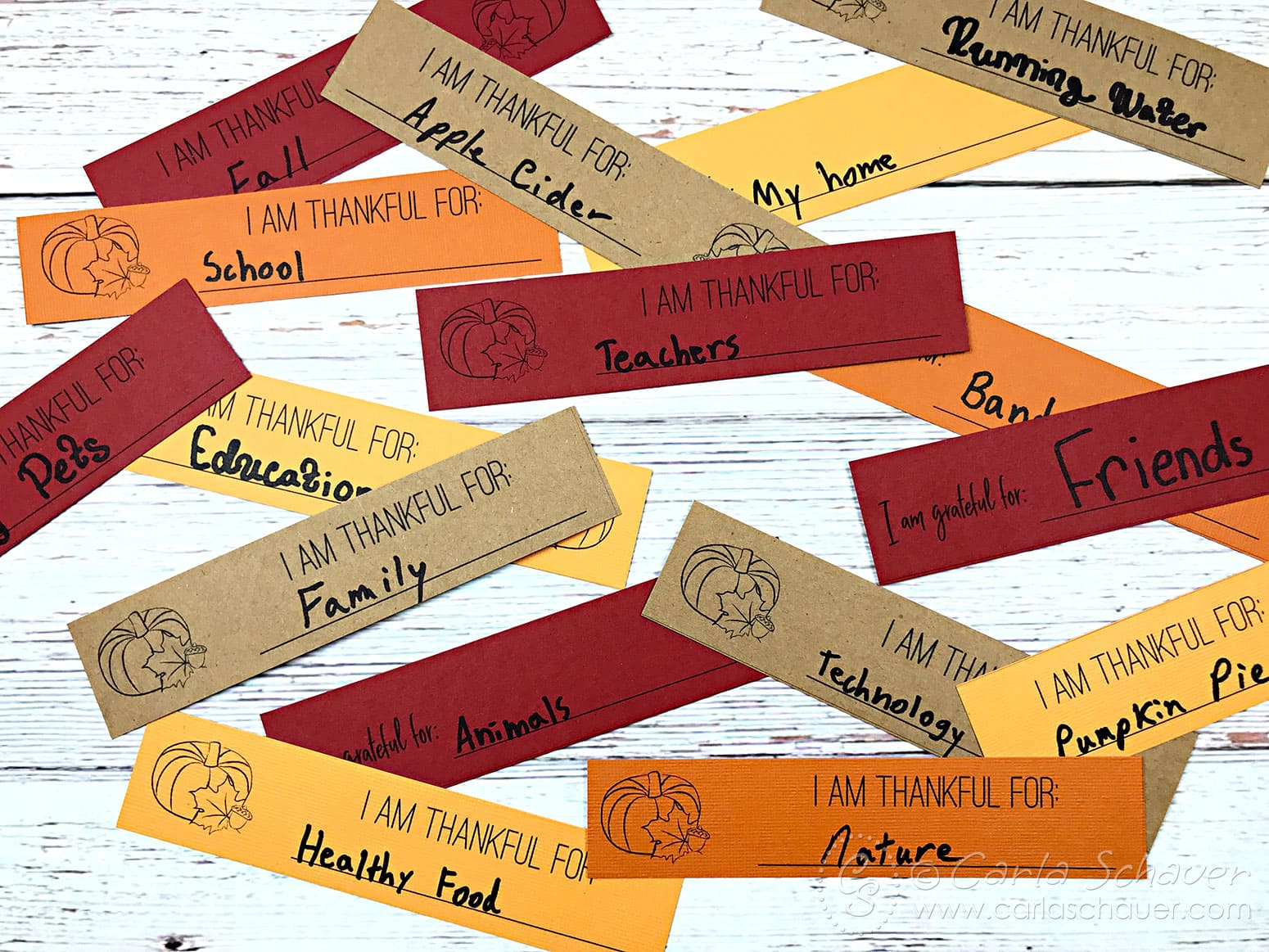 Fall colored paper strips with blessings written on them, scattered on white wood table.