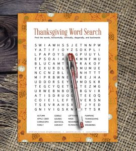 Thanksgiving word search with orange fall border, laying on burlap-covered wood table.