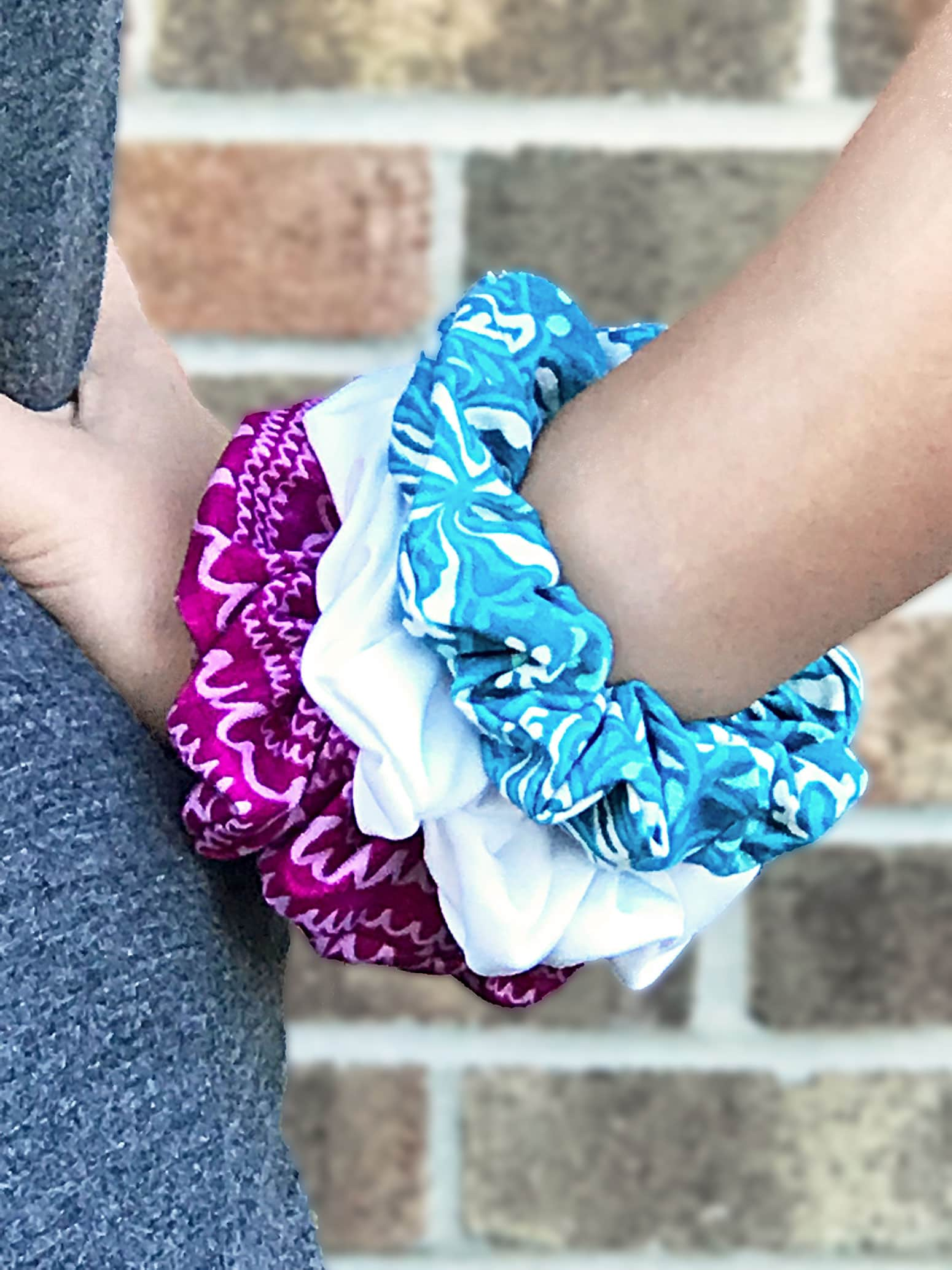 Pink, aqua, and white scrunchies on wrist.