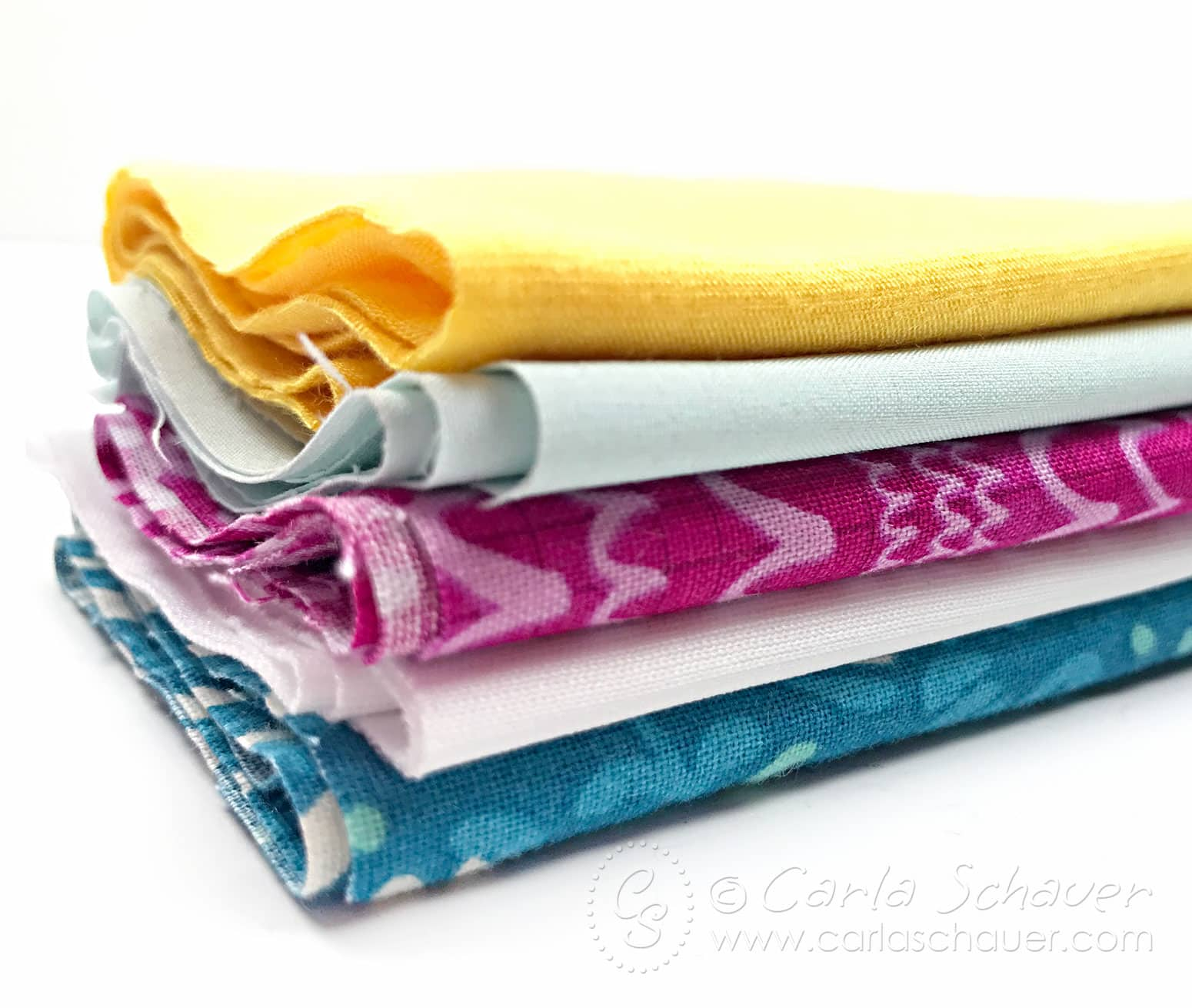 Stack of colorful fabrics on white background