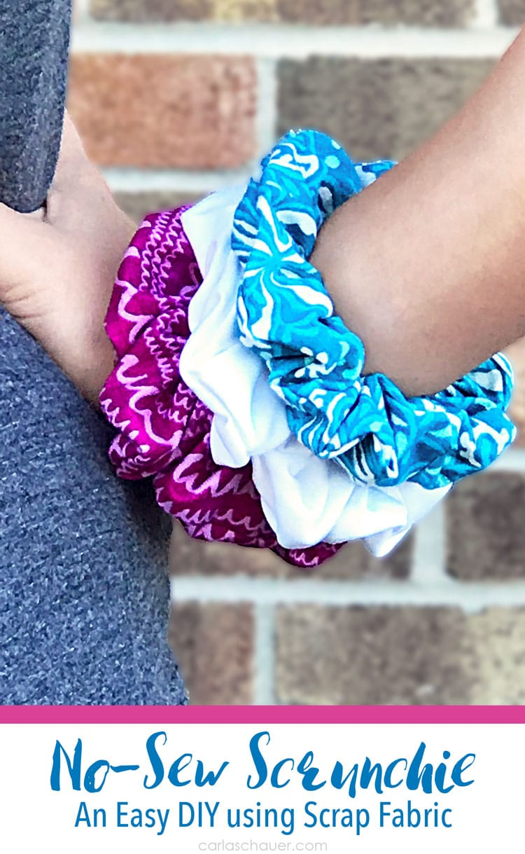 Pink, white, and blue hair scrunchies on girl's wrist.