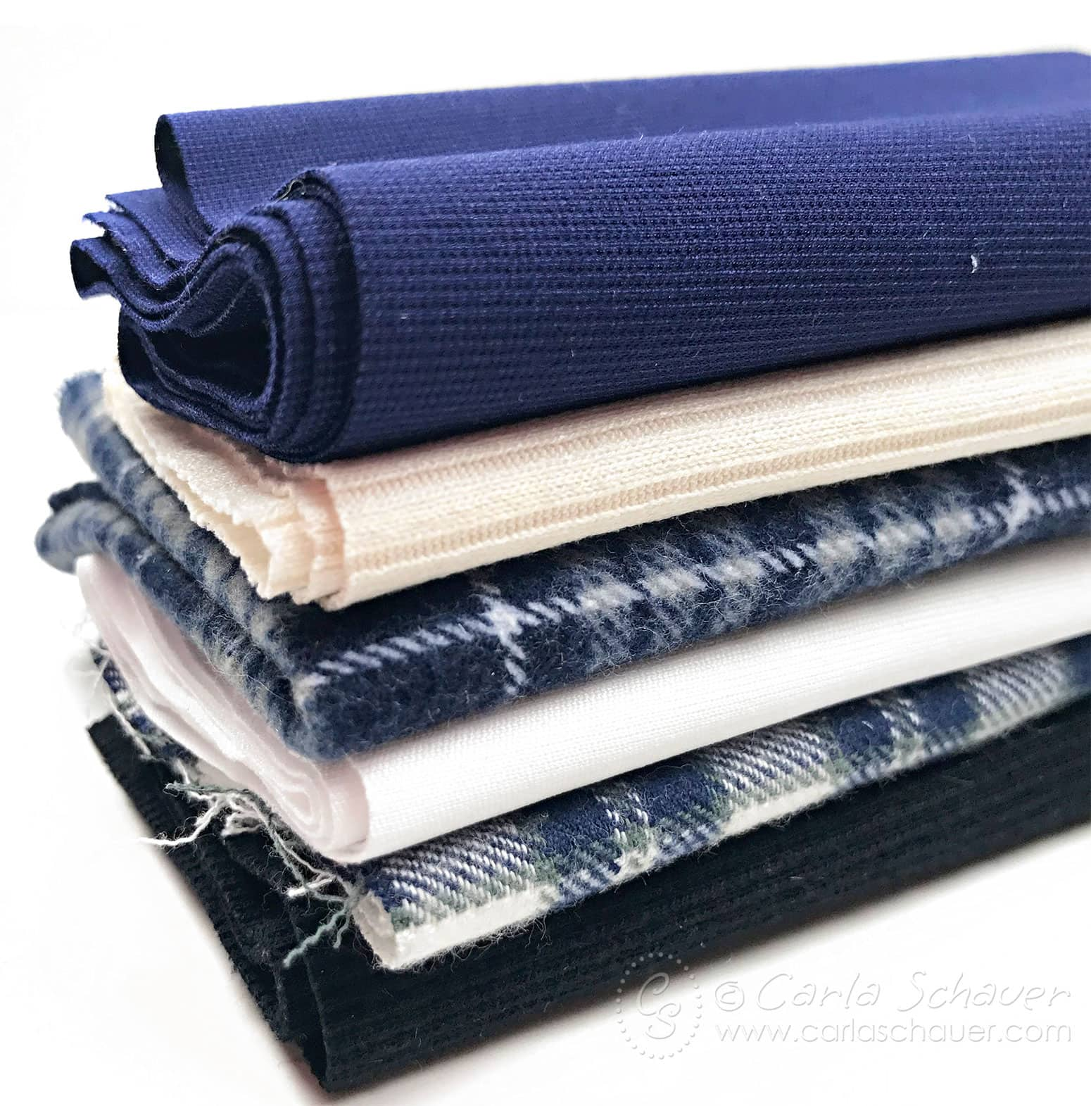 Stack of blue fabrics on white background.