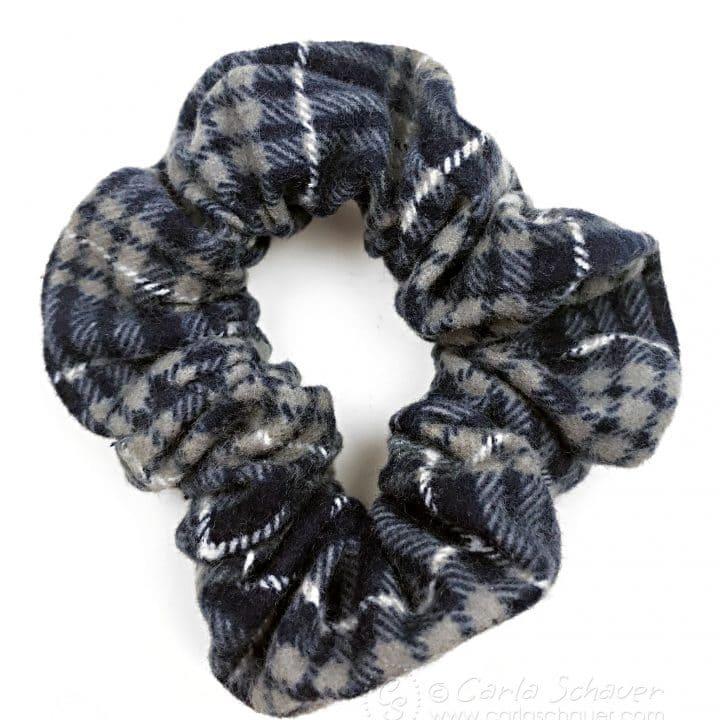 Plaid flannel hair scrunchie on white background.