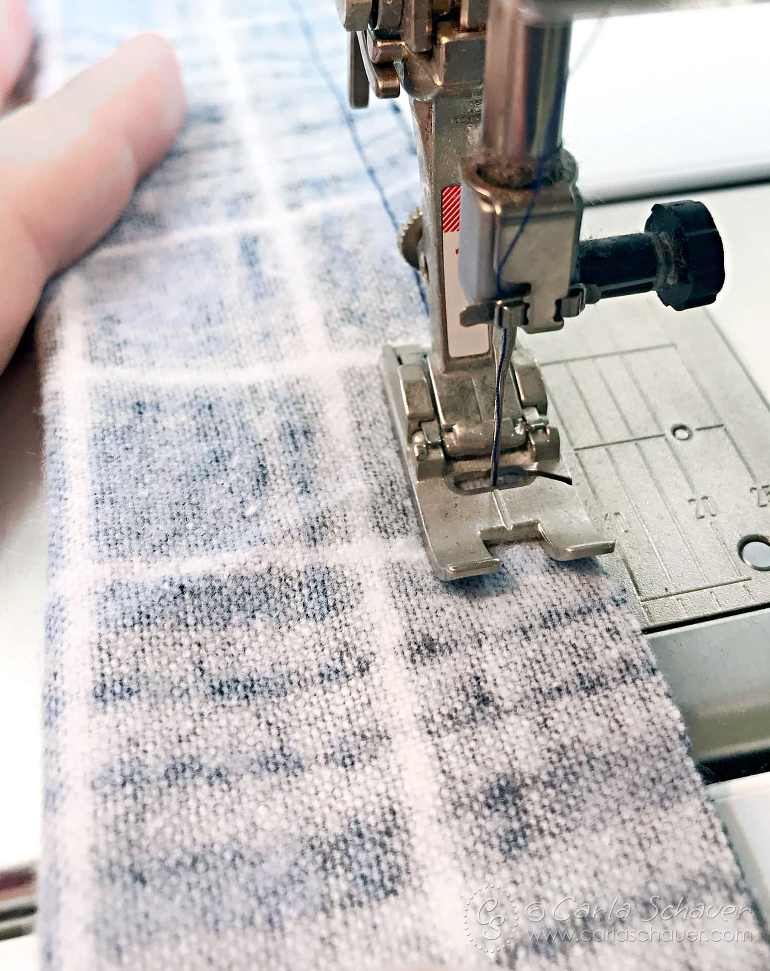 Plaid flannel fabric being sewn.