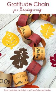 Interlocking fall colored paper strips making chain of gratitude. With felt leaves on white wood table.