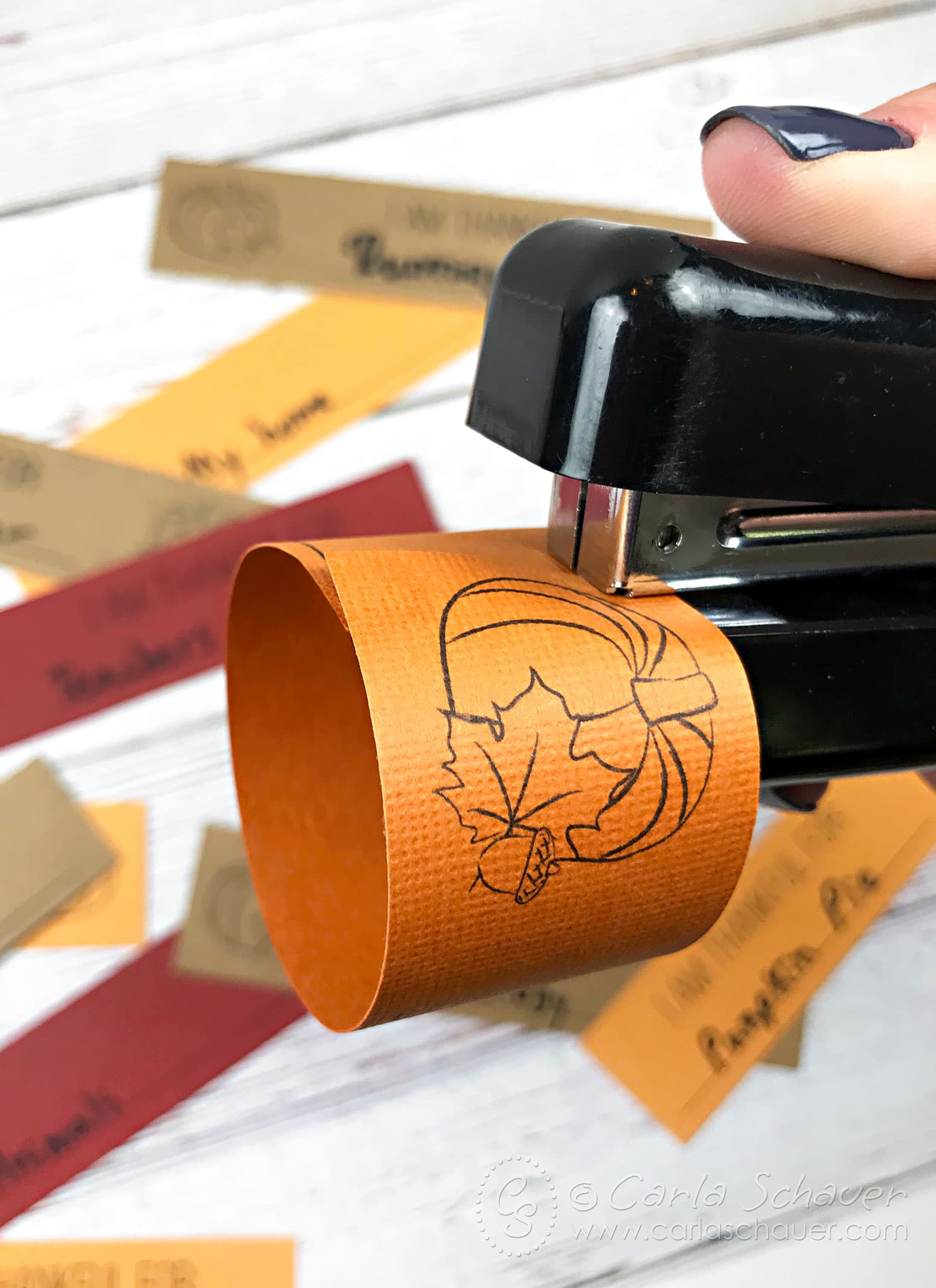 Stapler attaching paper gratitude strip ends to make a circle link.