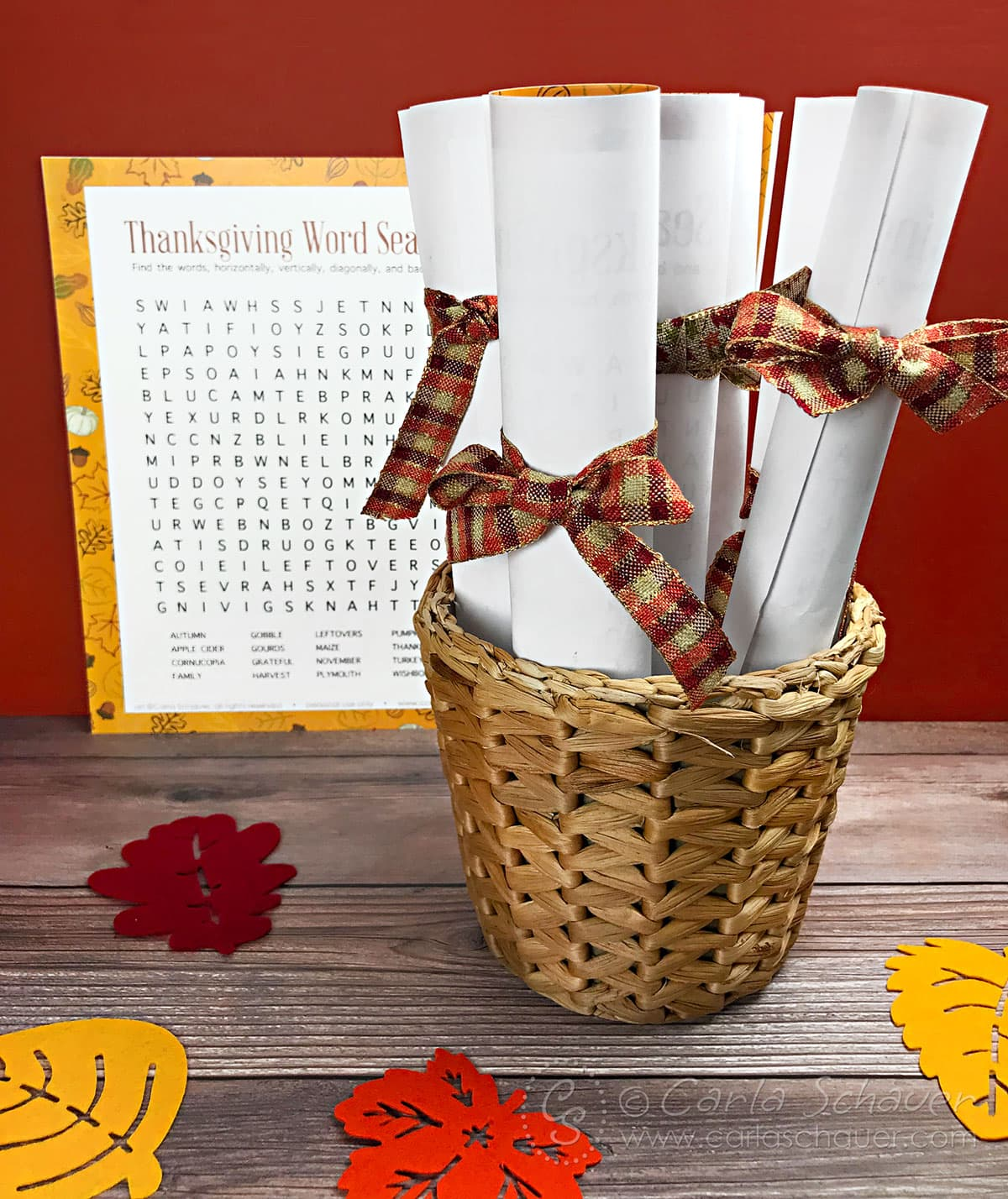 Rolled word search printables tied with fall ribbon, in basket, on wood table.