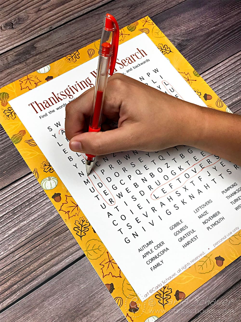 Hand circling words on Thanksgiving word search printable puzzle, on wood table.
