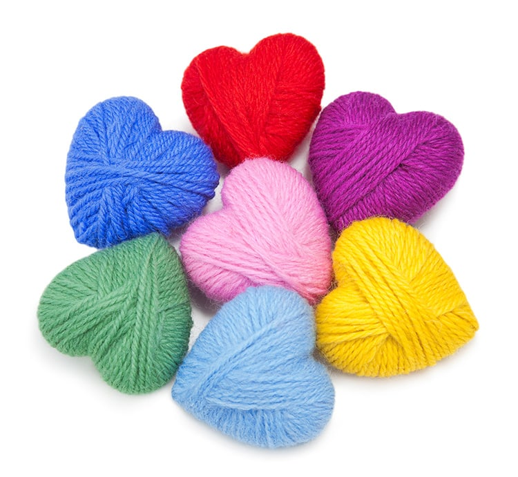 Yarn-wrapped hearts in multiple colors on white background