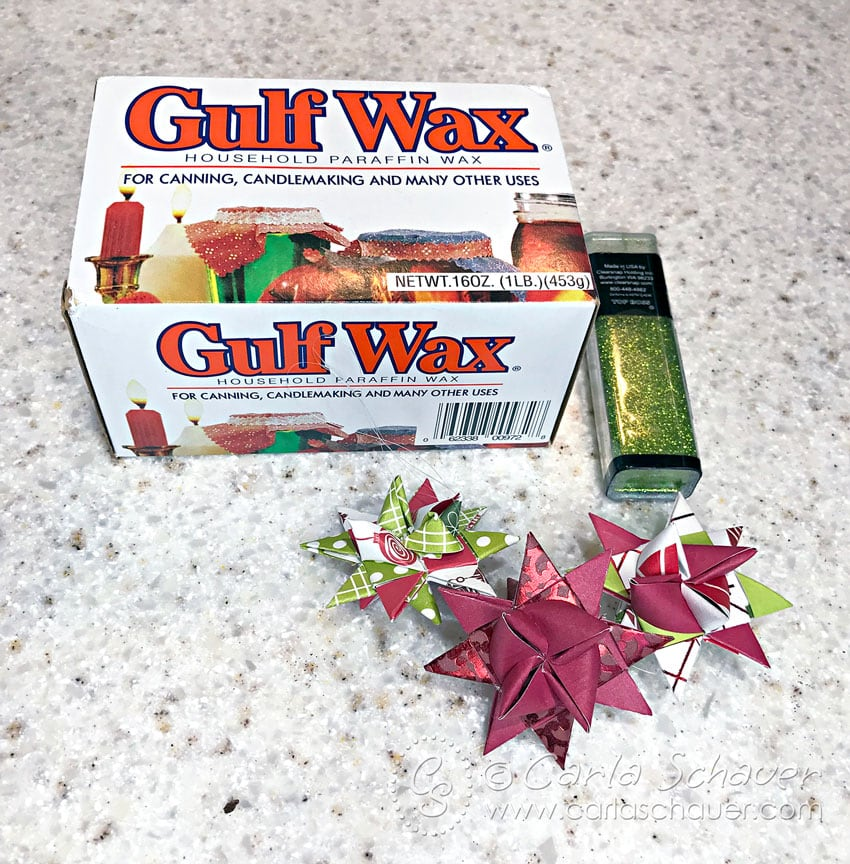 Wax, glitter, and folded paper stars. Supplies for dipping ornaments in wax.